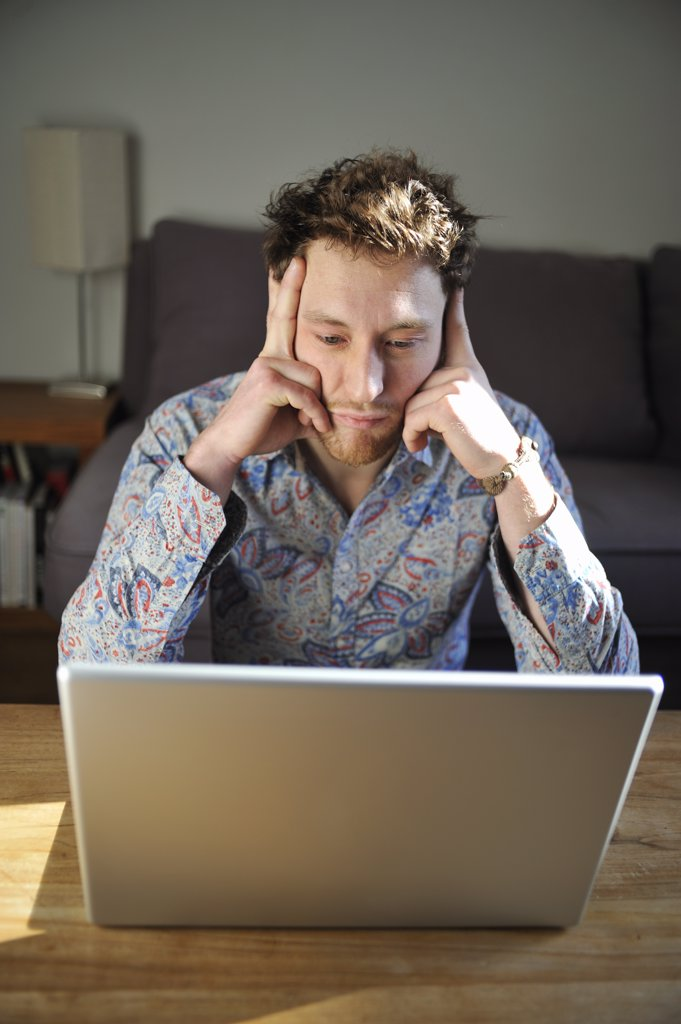 Man using a laptop at home : Stock Photo