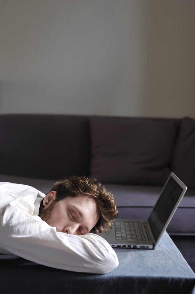 Stock Photo: 1606-171415 Man using a laptop at home, sleeping