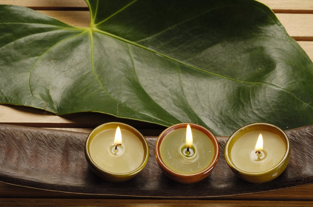 Stock Photo: 1606-171440 Three lightened candles, leaf and tropical seed