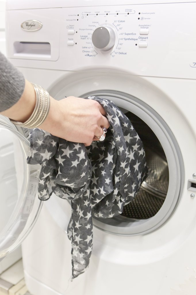 France, Paris, Darty, woman putting a scarf in the washing machine : Stock Photo
