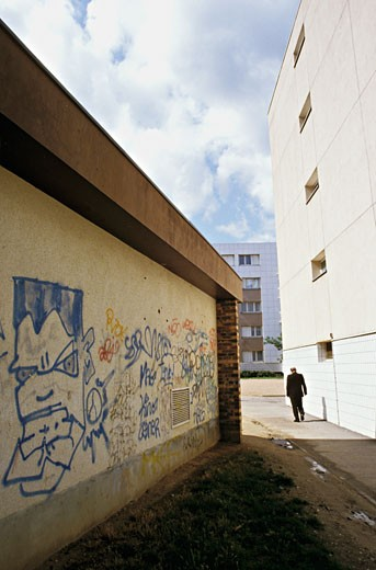 France, region of Paris, Yvelines, Les Mureaux, man walking in the street, graffiti : Stock Photo