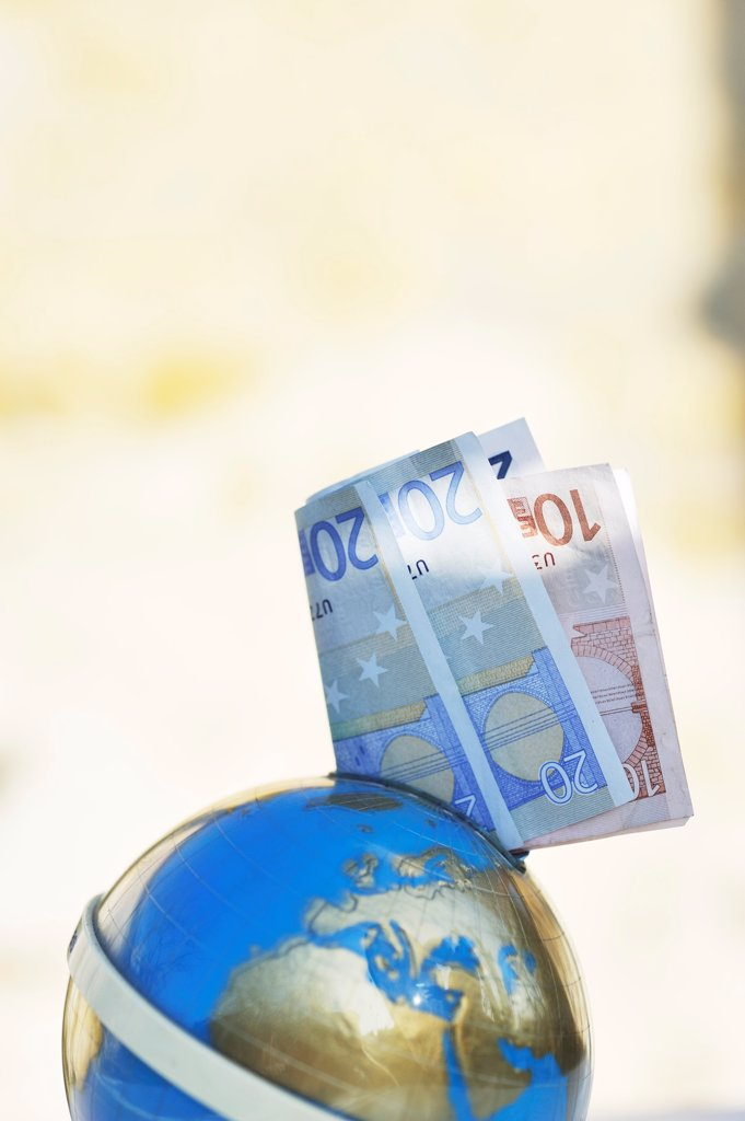 Stock Photo: 1606-178468 Euro bank-notes in a moneybox world globe