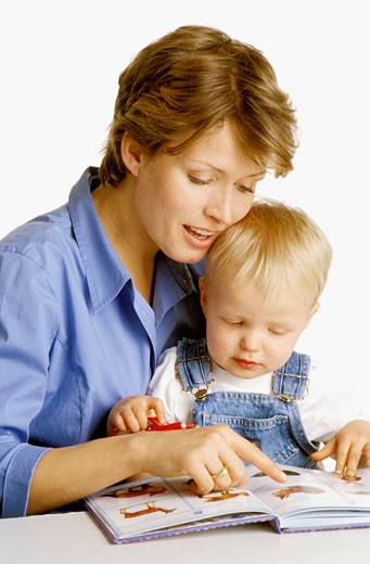 Woman with baby on her lap looking at a picture book : Stock Photo