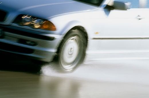 Close-up of a car on a wet road, tire, headlights : Stock Photo