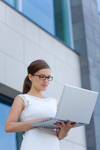 Pretty businesswoman with computer in front of a building : Stock Photo