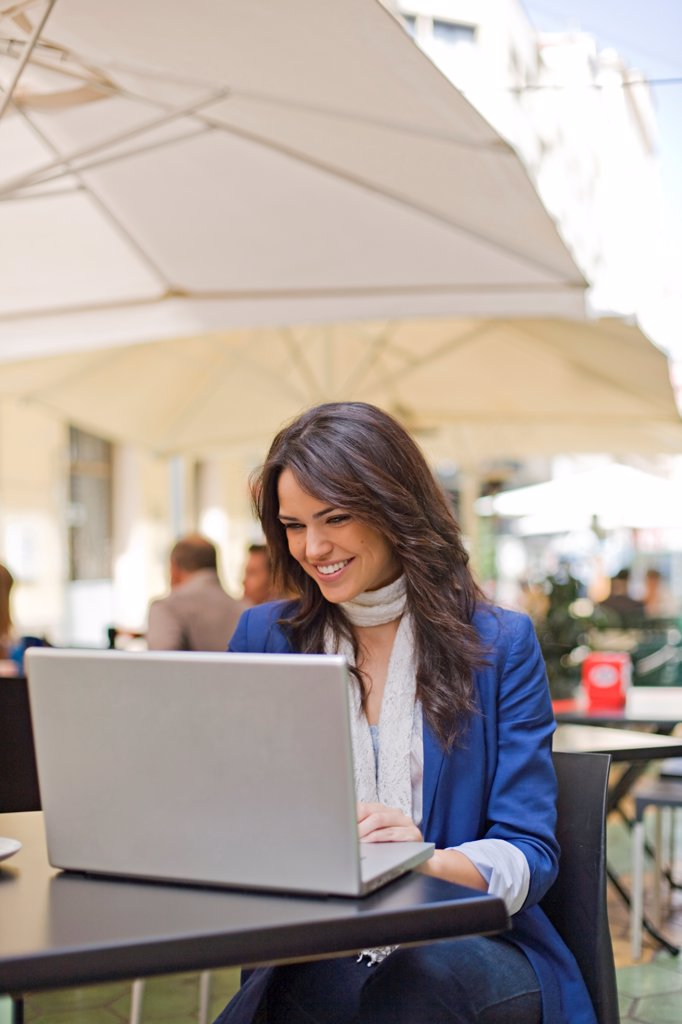 Pretty brunette woman with laptop in Cafe : Stock Photo