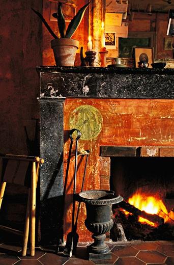Gros plan sur cheminée allumée dans intérieur ancien, murs orange, bougies, photos : Stock Photo