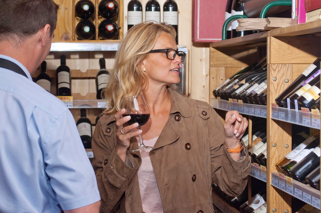 Stock Photo: 1606-190728 Occidental woman, selecting a bottle of wine,