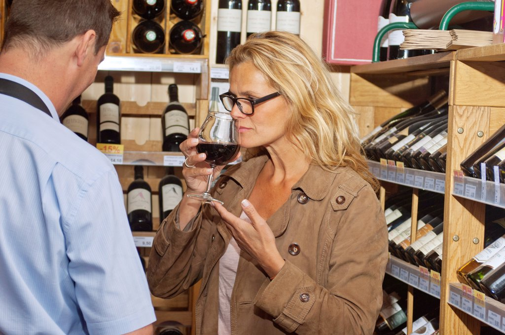 Stock Photo: 1606-190729 Occidental woman, selecting a bottle of wine,