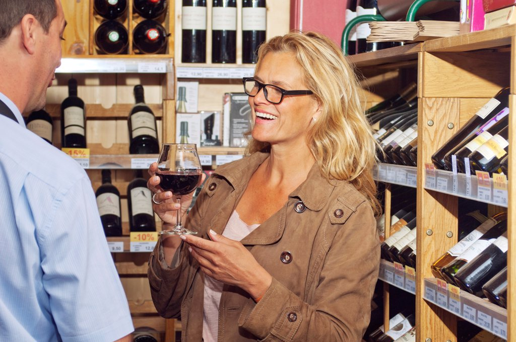 Occidental woman, selecting a bottle of wine, : Stock Photo