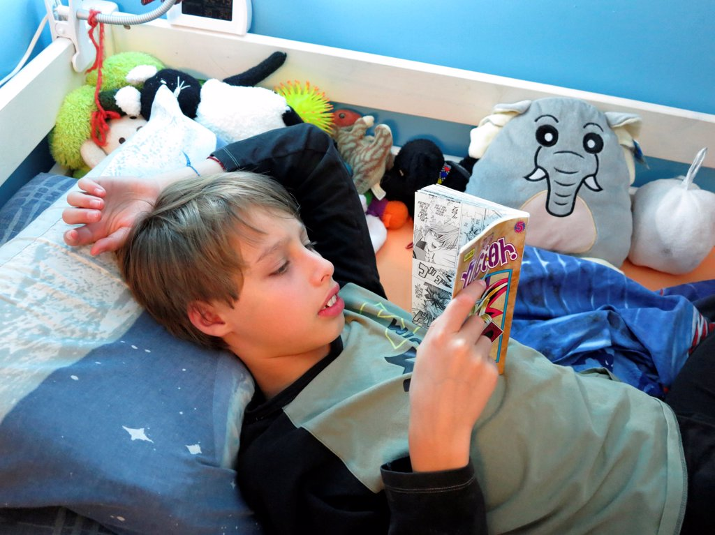 young teenager reading a book on his bed : Stock Photo