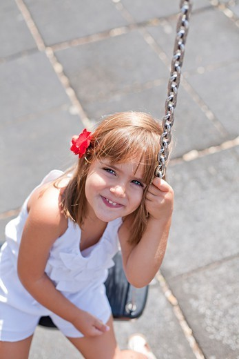 Cute girl in park on swing smiling at camera : Stock Photo