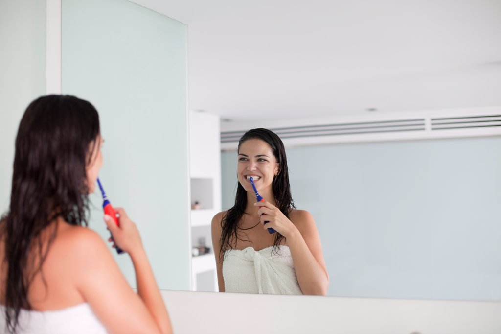 Brunette woman brushing her teeth in front of the mirror : Stock Photo