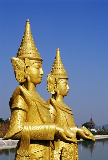 Burma, Mandalay, two golden statues, outdoors : Stock Photo