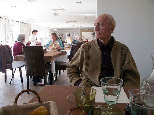 Stock Photo: 1606-193003 Old Man Sitting At A Table In A Retirement Home Dining Room