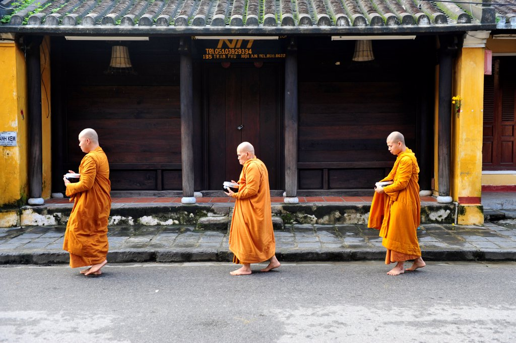 A Group Of Monks Are Walking In A Street Of Hoi An To Receive The Food Offering, Vietnam, South East Asia, Asia : Stock Photo