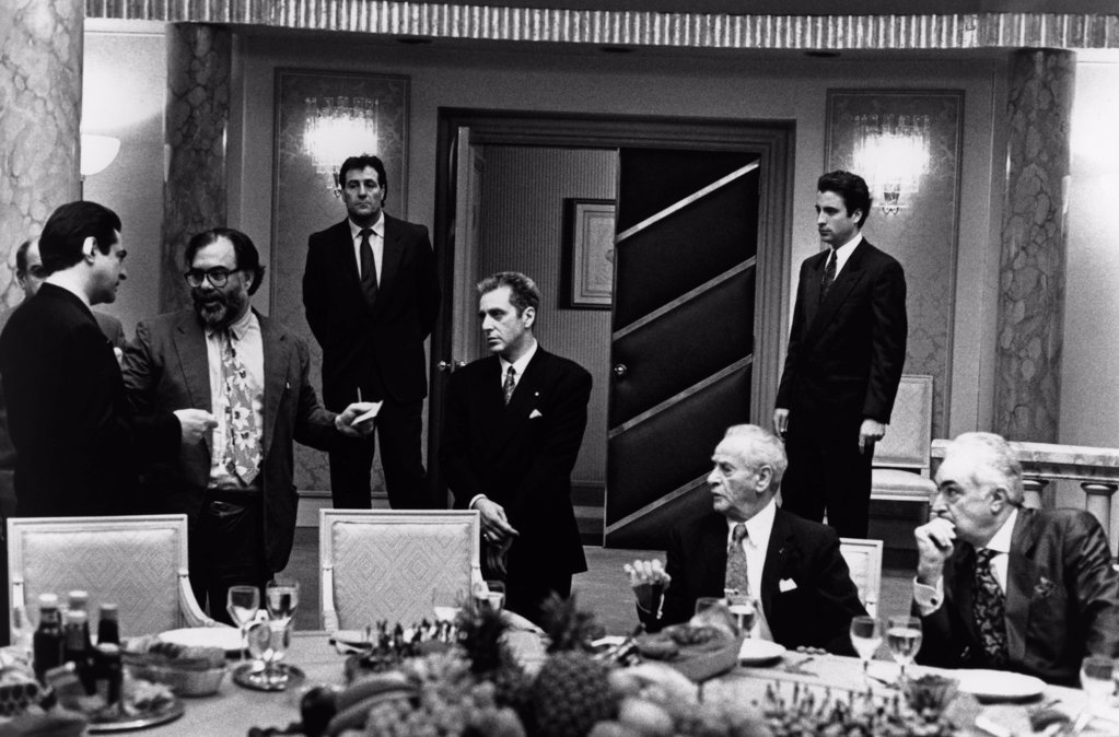 On the set, Francis Ford Coppola directs Joe Mantegna (left), Al Pacino (center), Andy Garcia (standing right) and Eli Wallach (seated second from right), The Godfather: Part III, 1990 directed by Francis Ford Coppola (Paramount Pictures) : Stock Photo