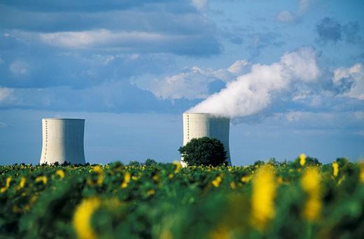 86. Centrale nucléaire de Civaux, 2 cheminées dont une fumant, champ de tournesols au premier plan, nuages : Stock Photo