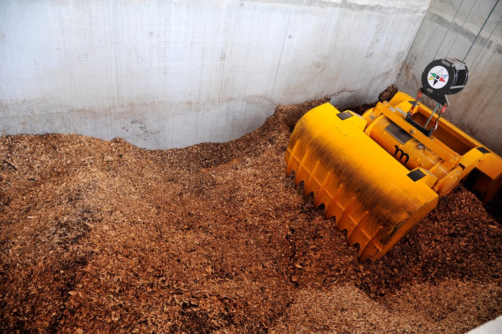 France, biomass boiler room supplied with wood waste for district heating in Nantes, storage of wood waste. : Stock Photo