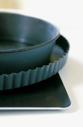 Stock Photo: 1606-21634 Gros plan sur moules à gateaux en métal anti-adhésif, empilés (moule à manqué, moule à tarte et plat carré)