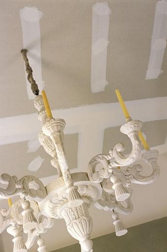 Stock Photo: 1606-21915 Gros plan sur lustre blanc suspendu, bougies jaunes, plafond avec bandes de plâtre