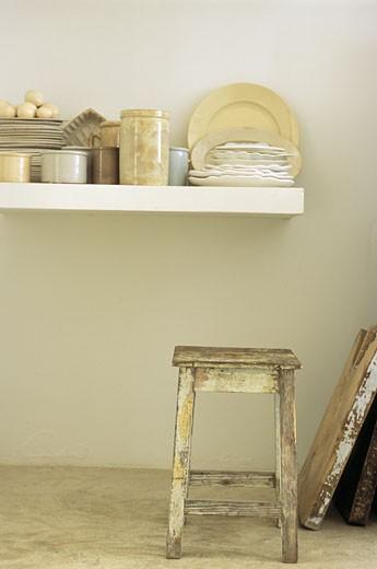Intérieur cuisine, pots en grès et piles d'assiettes sur étagère blanche, tabouret en bois ancien : Stock Photo