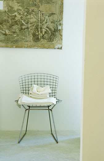 Stock Photo: 1606-22059 Intérieur, savon sur pile de serviettes blanches sur chaise en métal dans couloir, dessin ancien sur mur