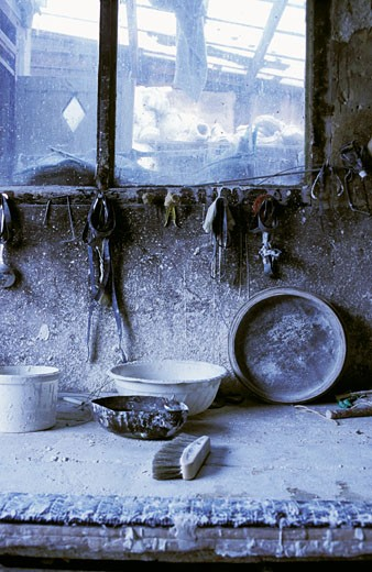 Intérieur atelier de moulage, gros plan sur accesssoires et  outils sur plan de travail, éclaboussures de plâtre, fenêtre : Stock Photo