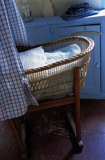 Gros plan sur berceau ancien en osier devant meuble peint en bleu, rideaux à carreaux : Stock Photo