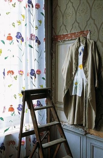 Stock Photo: 1606-22155 Gros plan sur rideau fleuri devant fenêtre, escabeau ancien, veste ancienne en lin sur cintre accroché à linteau de porte, murs en réfection