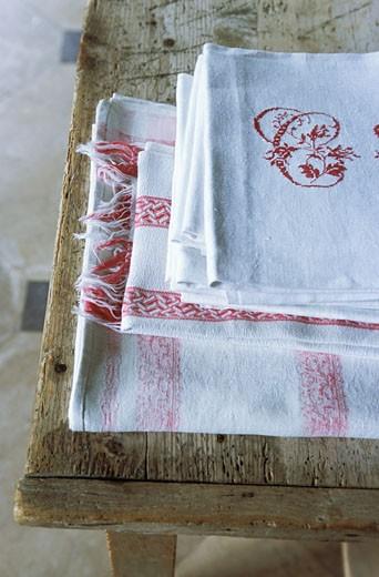 Gros plan sur torchons rouges et blancs en lin, pliés sur meuble en bois ancien, lettre C brodée sur torchon du dessus : Stock Photo