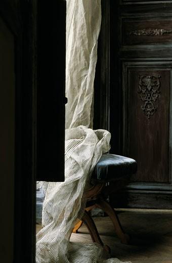 Intérieur ancien, détail buffet en bois sombre orné de ferrures, rideau rayé noir/blanc sur chaise : Stock Photo