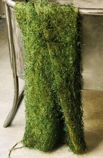 Gros plan sur tissu vert fantaisie, avec bouclettes d'aspect végétal, sur dossier d'un fauteuil en métal, intérieur : Stock Photo