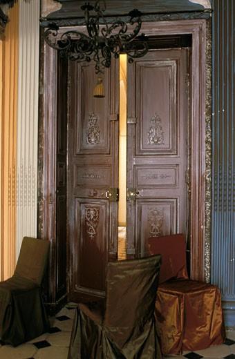 Stock Photo: 1606-22247 Intérieur ancien, 3 chaises avec housses en taffetas devant porte marron sculptée, entrouverte, lustre en fer forgé