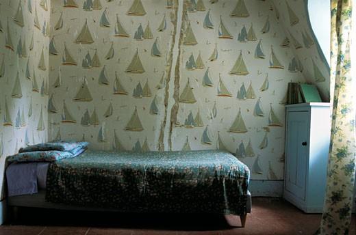 Intérieur chambre ancienne, papier peint représentant voiliers, dessus de lit imprimé vert, rideau, petit meuble au fond : Stock Photo
