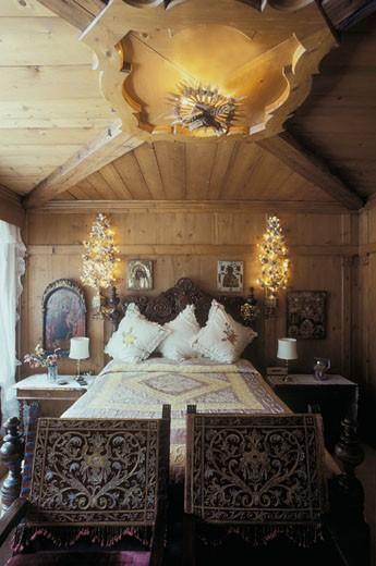 Cortina d'Ampezzo, intérieur chambre d'un chalet ancien, icones sur mur en bois au fond, 2 chaises ouvragées au 1er plan devant lit : Stock Photo