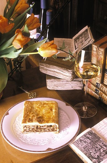Composition part de gateau feuilleté au chocolat sur assiette blanche, livres anciens et bouquet de tulipes sur table, verre de vin blanc : Stock Photo