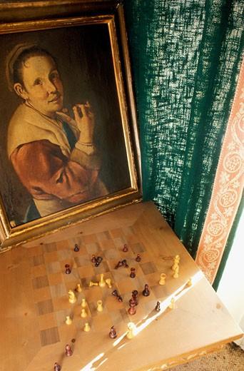 Stock Photo: 1606-22354 Gros plan sur jeu d'échecs devant fenêtre avec rideau vert, tableau ancien représentant femme mangeant fruits