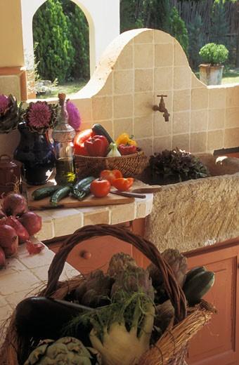 Cuisine d'été, salade dans évier en pierre, légumes sur plan de travail, bouquet d'artichauts en fleur, panier de légumes au 1er plan : Stock Photo