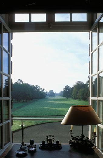 Gros plan sur bibelots anciens et lampe sur rebord de fenêtre ouverte, donnant sur parc avec pelouses verdoyantes : Stock Photo