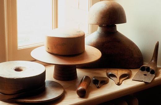 Intérieur atelier de chapelier, formes de chapeaux en bois et outils devant fenêtre : Stock Photo