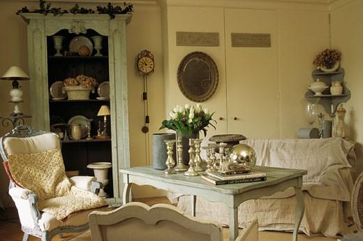Stock Photo: 1606-22915 Intérieur salon ancien, canapé et fauteuils autour table, livres, bouquet de tulipes et bougeoirs sur table, bibelots dans meuble au fond