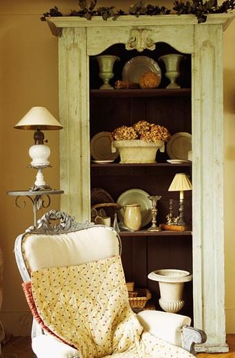 Stock Photo: 1606-22919 Intérieur salon ancien, bibelots sur étagères d'un meuble en bois, fauteuil au 1er plan, lampe sur sellette