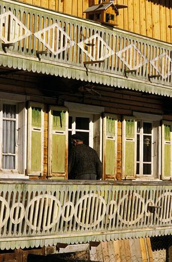 74. Vallée d'Abondance, détail facade d'un chalet ancien, volets verts, homme âgé entrant, petit chalet sur balcon : Stock Photo