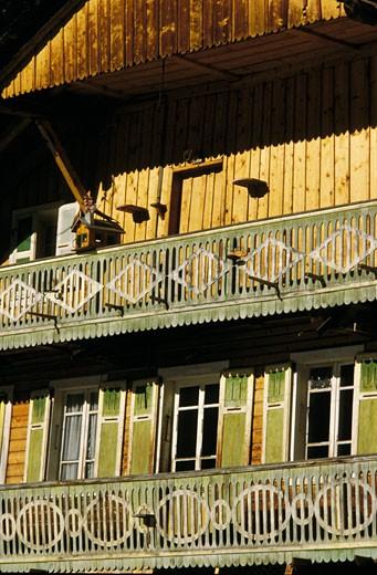 Stock Photo: 1606-22929 74. Vallée d'Abondance, détail facade d'un chalet ancien à 2 étages, volets verts, petit chalet sur balcon