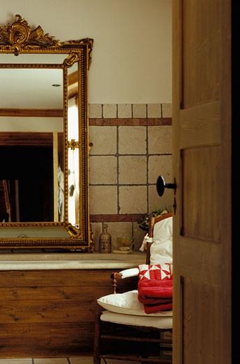 Val d'Isère, Terrini, intérieur salle de bains, grand miroir au dessus de la baignoire avec coffrage en bois, porte ouverte au 1er plan : Stock Photo