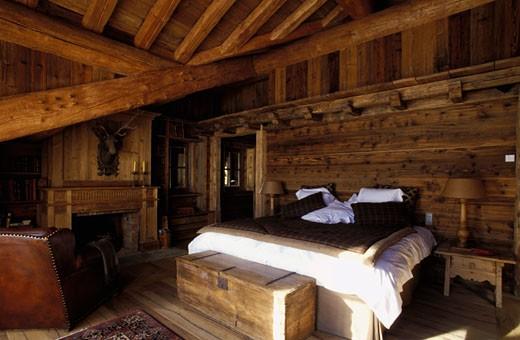 Stock Photo: 1606-24306 Val d'Isère, intérieur chambre, murs en lambris, coffre ancien au pied du lit, cheminée en bois, fauteuil en cuir