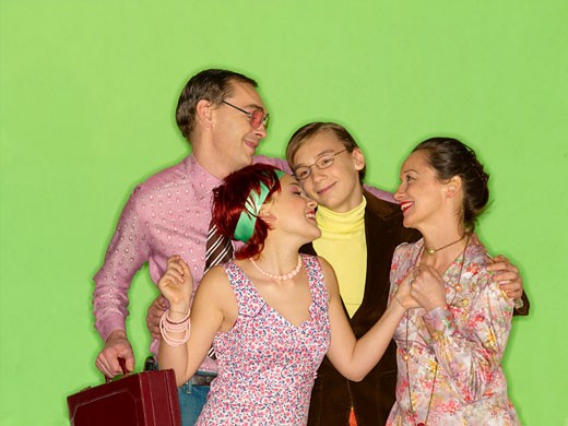 Stock Photo: 1606-24423 Man and teenage boy smiling, woman and young woman smiling at each other