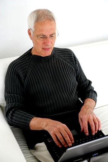 IN*Pierre utilisant ordinateur portable, assis sur canapé blanc dans salon, lunettes : Stock Photo
