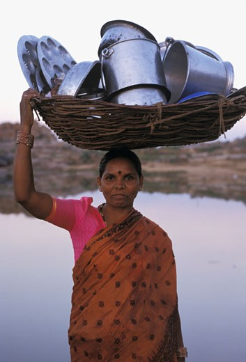 India, Karnataka, Hampi, river Tungabhadra, woman carrying dishes : Stock Photo